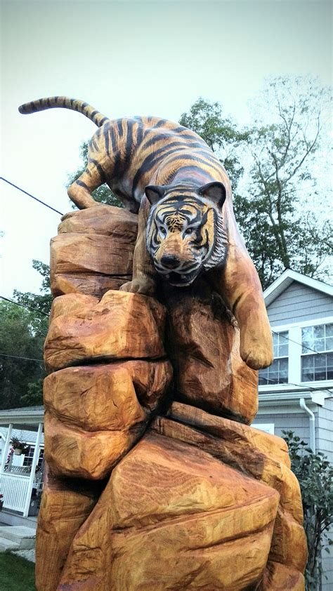 Chainsaw carving of Tiger climbing down rocks – Time lapse